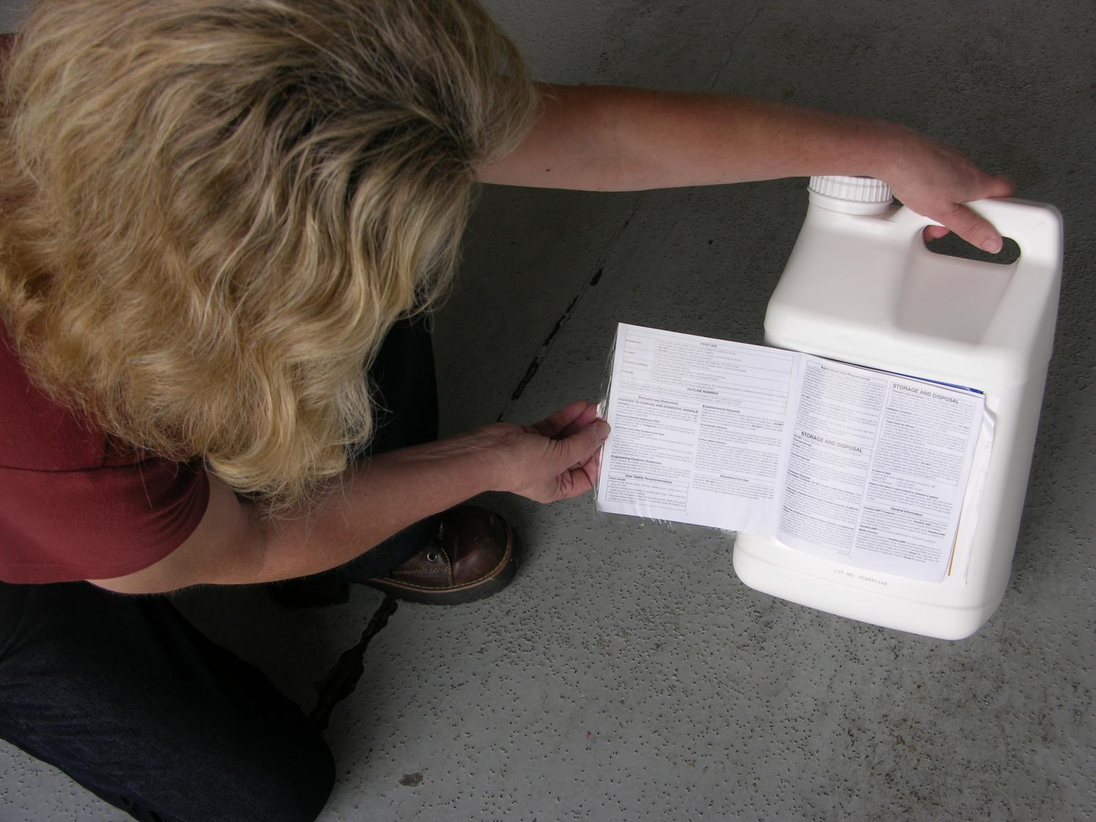 An Applicator inspects a pesticide label